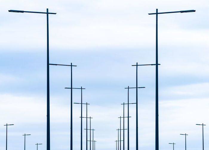 Minimalism Minimalistic Symmetry Modern Technology In A Row Cloud - Sky Parallel Sky Low Angle View No People Nature Outdoors Day Communication Connection Antenna - Aerial Metal Street Light Lighting Equipment Silhouette Electricity  Pole Tall - High Architecture Electrical Equipment Power Supply