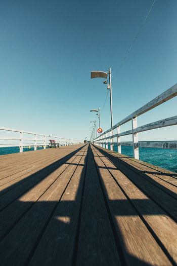 Pier in a small fishing town against clear blue sky