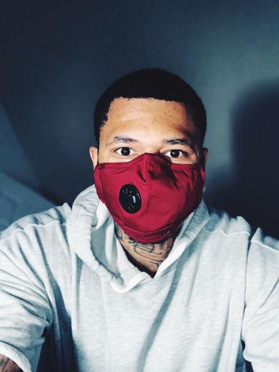 Portrait of man wearing flu mask against wall