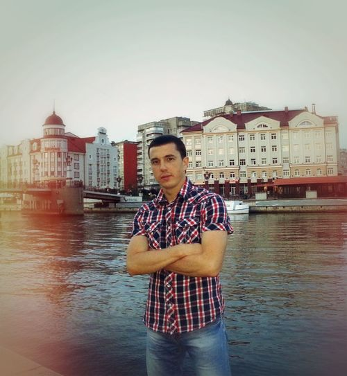 Portrait of man standing against river in city