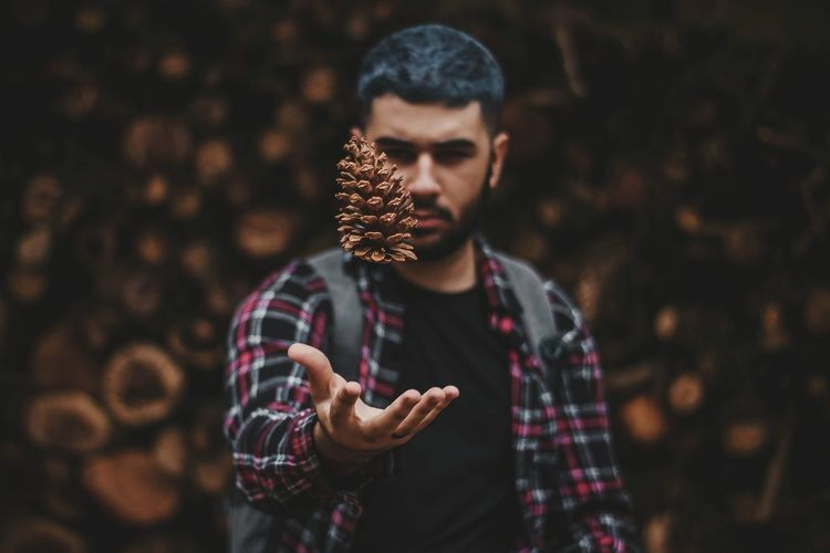 Young Man Playing With Pine Cone While Standing Outdoors