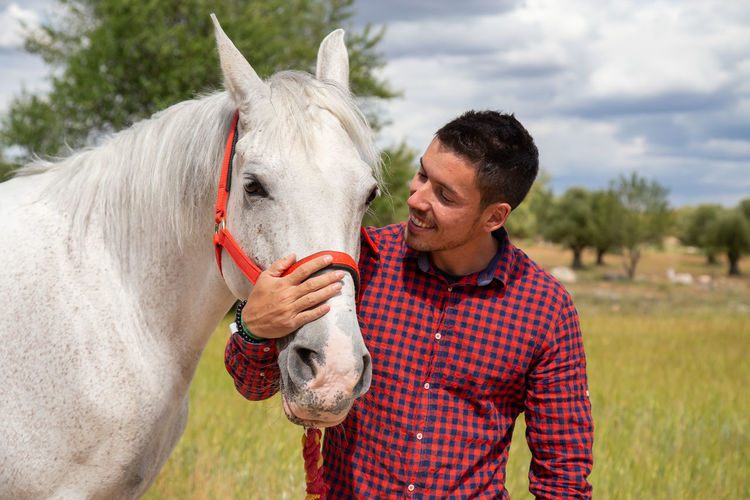 Young man with horse on field