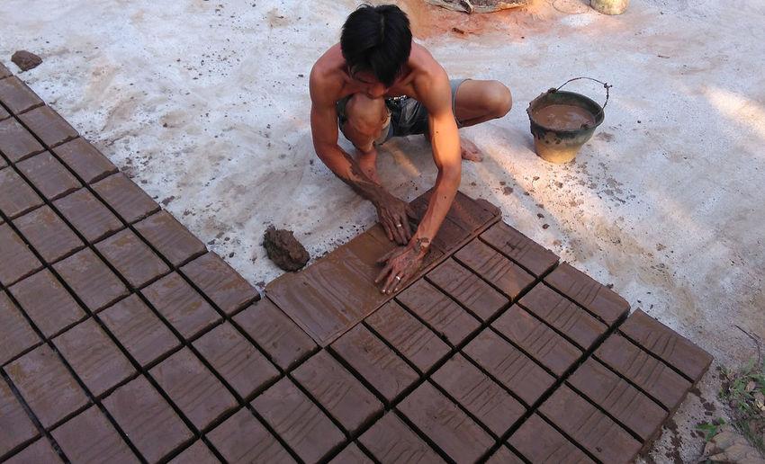 High Angle View Of Man Preparing Bricks On Ground