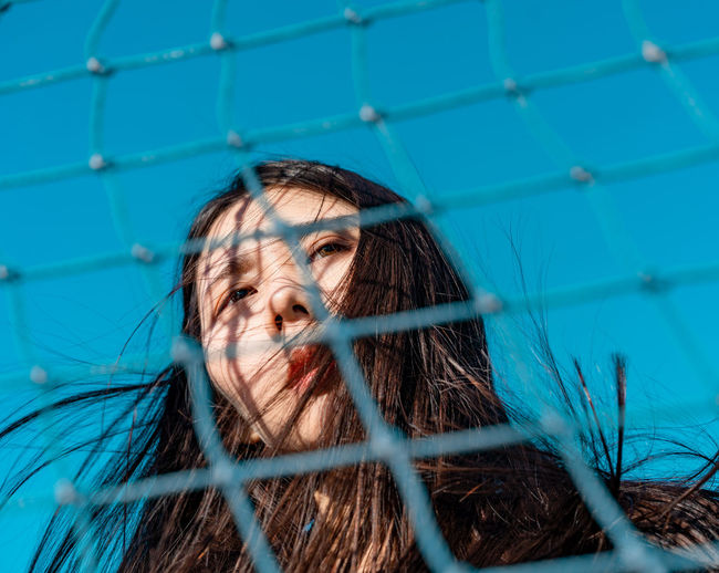 Low angle view of woman seen through net