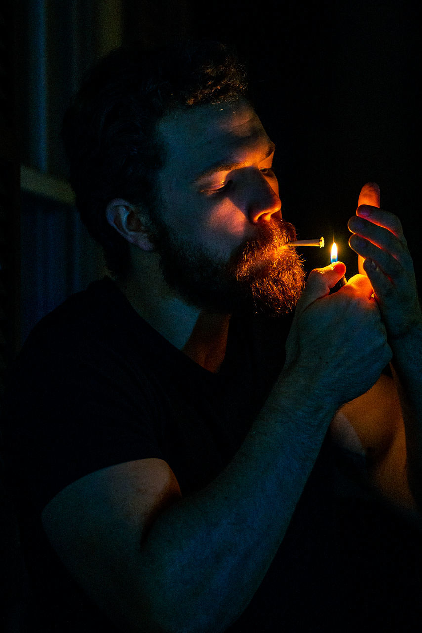 MIDSECTION OF MAN HOLDING ILLUMINATED FIRE