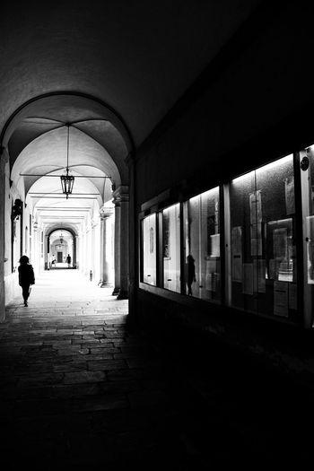 People walking on footpath amidst illuminated building