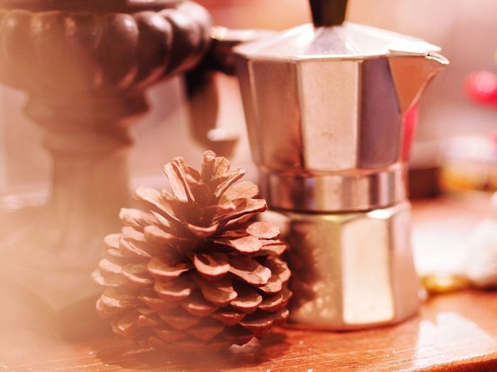 Close-Up Of Coffee Maker With Pine Cones On Table