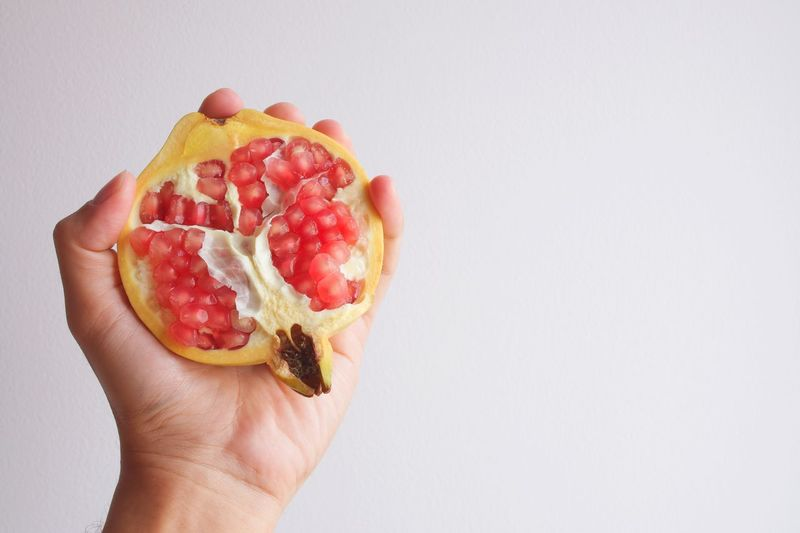 Close-up of hand holding strawberry against white background