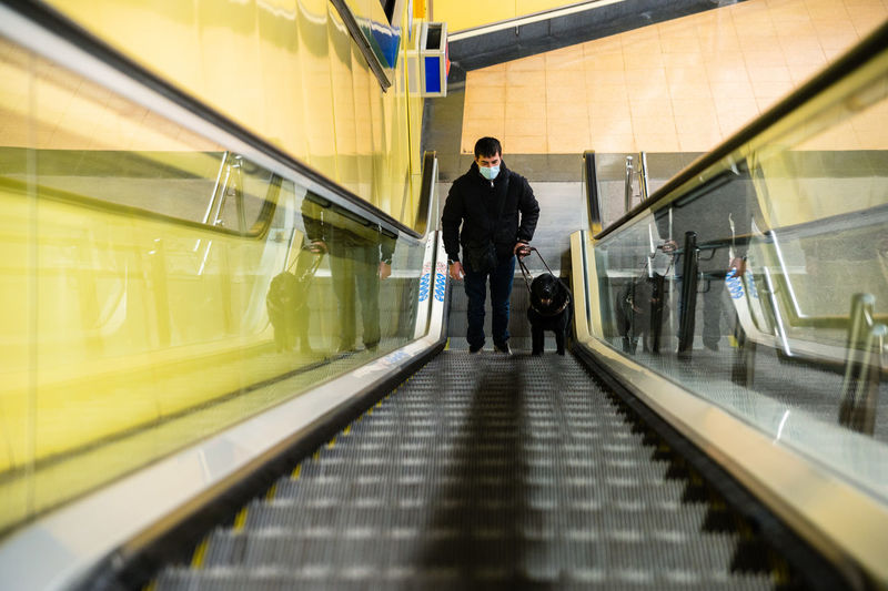 Rear view of man on escalator at railroad station