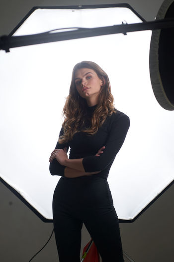 Portrait Of Young Woman With Arms Crossed Standing Against Studio Light