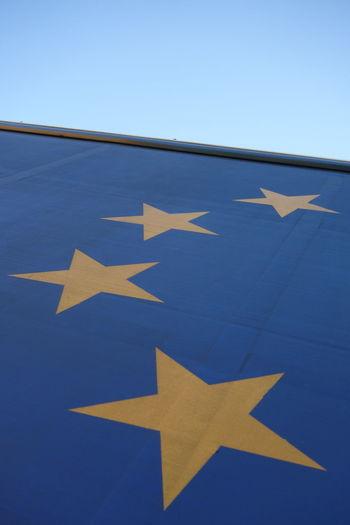 Close-up of arrow sign against blue sky