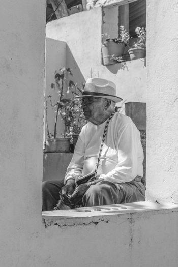 Senior Man Wearing Hat And Eyeglasses While Sitting On Chair Seen Through Window