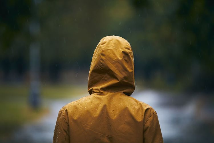 Rear view of man wearing raincoat standing outdoors