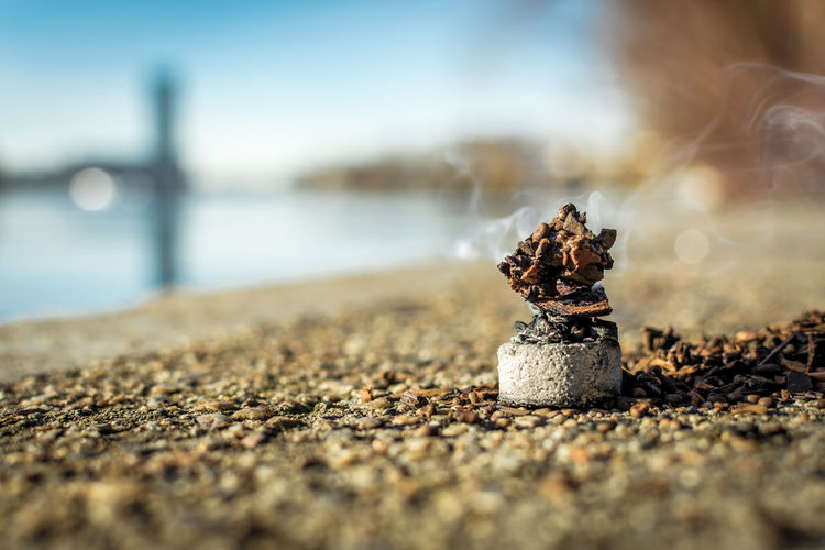 Pebble Creativity Religion Representation Tranquility Solid Cigarette  Rock Single Object Sunlight Land Sea Beach Sky Water Close-up Selective Focus Outdoors Day No People Nature Still Life Human Representation Social Issues Sign