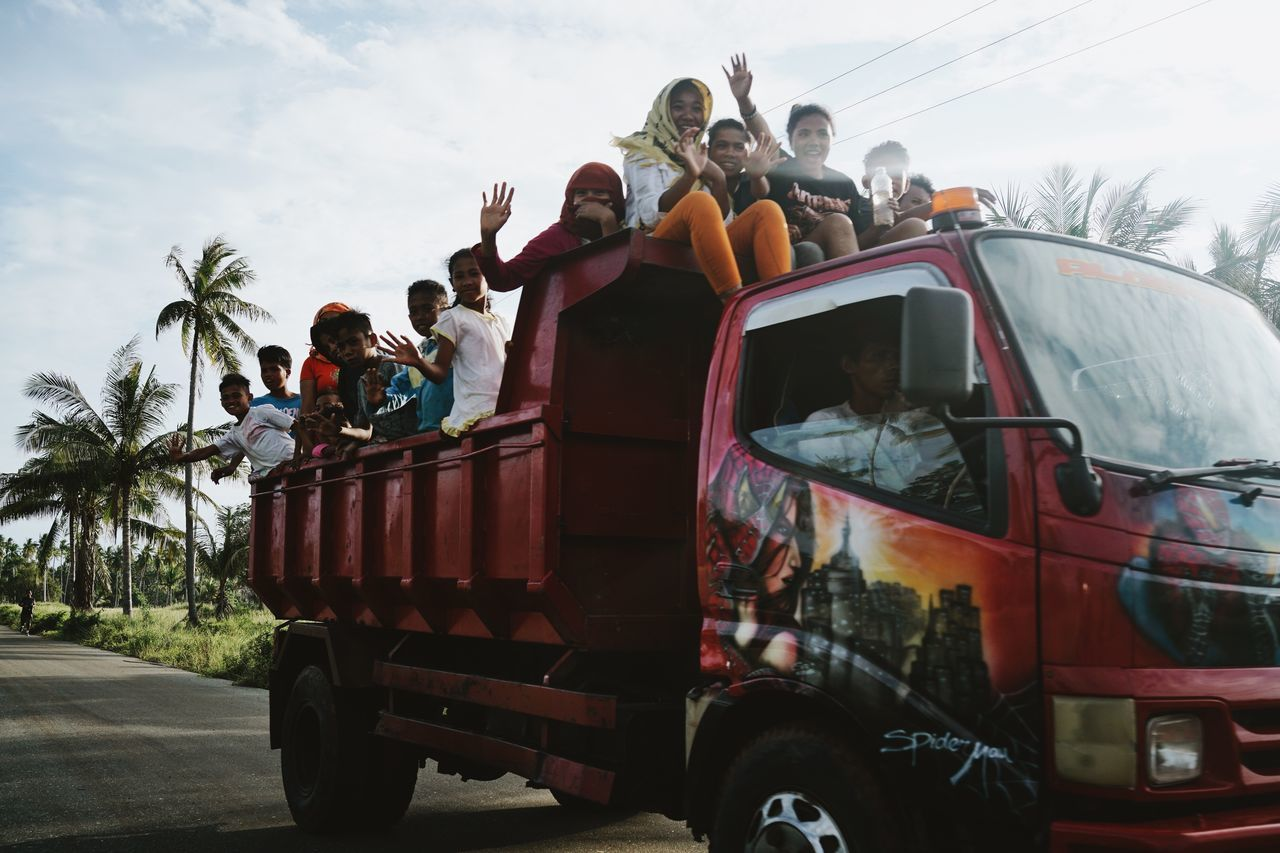 real people, transportation, mode of transport, men, land vehicle, outdoors, day, sky, road, lifestyles, occupation, women, tree