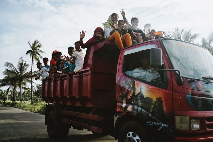 ASIA Children Daily Life Day Driving Driving By Happy INDONESIA Kids Maluku  Moluccas Morotaiisland On The Road Painted Trucks Palm Trees People Red Truck Snapshot Sunny Day Transportation Travel Truck Vehicle Waving The Photojournalist - 2017 EyeEm Awards The Street Photographer - 2017 EyeEm Awards Sommergefühle An Eye For Travel