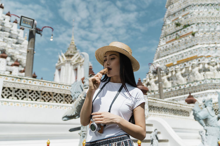 Woman eating ice cream against temple