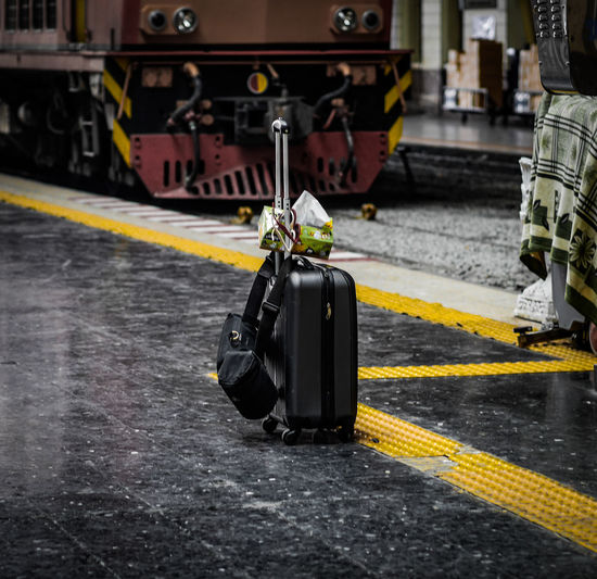 Suitcase against train at railroad station