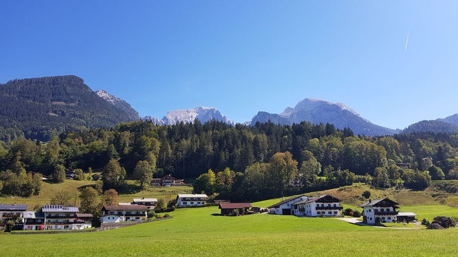 Beautiful landscape of mountains, village houses and green forests in Austria Architecture Beauty In Nature Building Exterior Built Structure Clear Sky Day Europe Field Forest Grass Green Color Growth Land Landscape Mountain Mountain Range Mountains Nature No People Outdoors Plant Scenics - Nature Sky Tree Village Houses