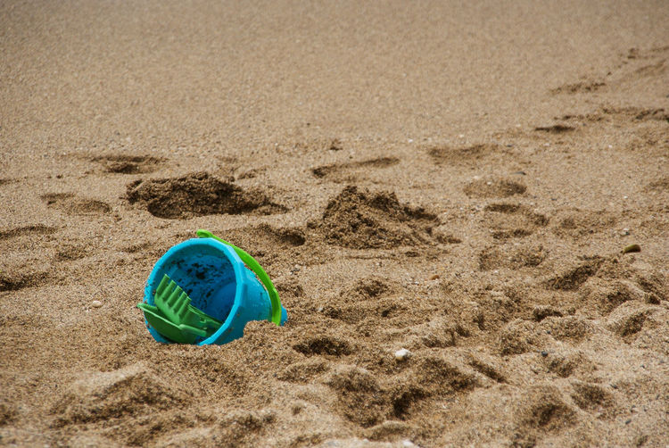 Close-up of bucket on sand at beach