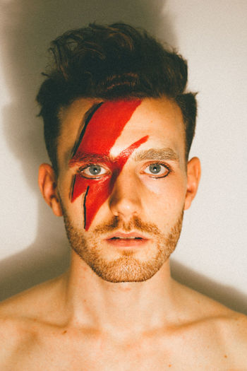 Close-Up Portrait Of Young Man With Red Face Paint While Standing Against Wall