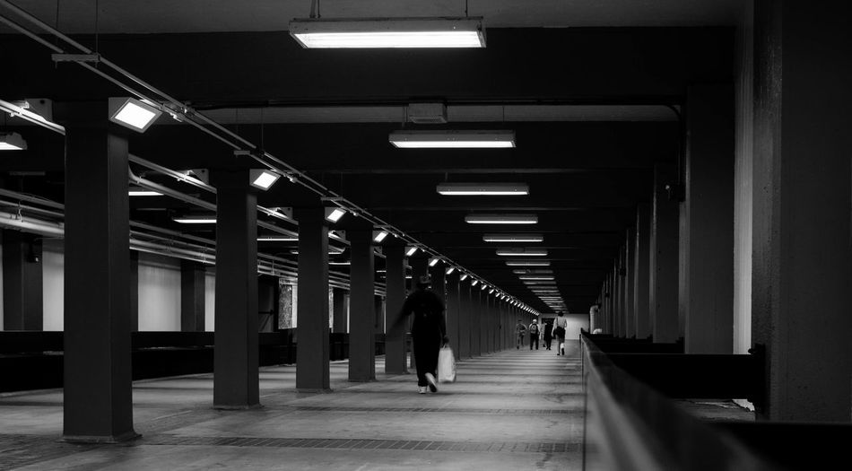 Man walking in illuminated corridor of building