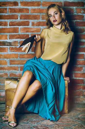 Full length portrait of young woman holding diary while sitting against brick wall