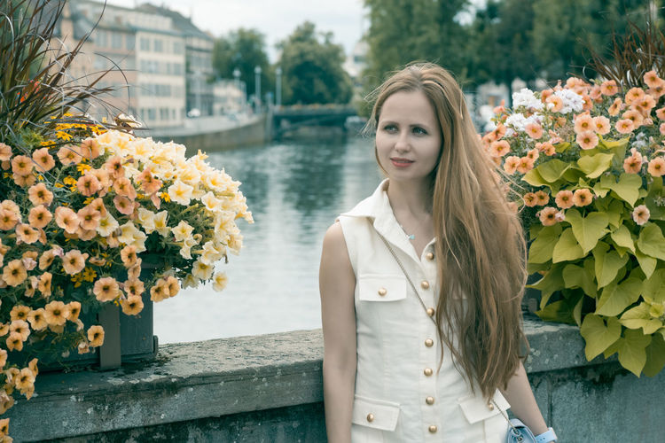 Woman looking away by flowers against canal in city