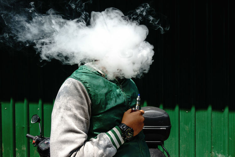 Man holding electronic cigarette while face covered with smoke