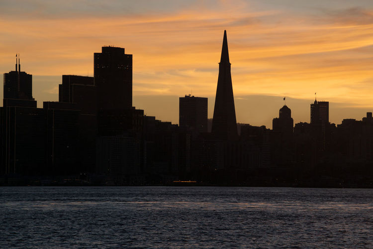 Standing at Treasure Island's observation deck, I watched the beautiful sunset at the Embarcadero area of San Francisco. The sun setting behind the bildings produced a beautiful silhouette, and stunning, warm colors. Sunset Building Exterior Architecture Sky City Waterfront Skyscraper Urban Skyline Orange Color Silhouette Travel Destinations No People Tall - High Cloud - Sky Cityscape Modern Outdoors Financial District  San Francisco California USA Treasure Island