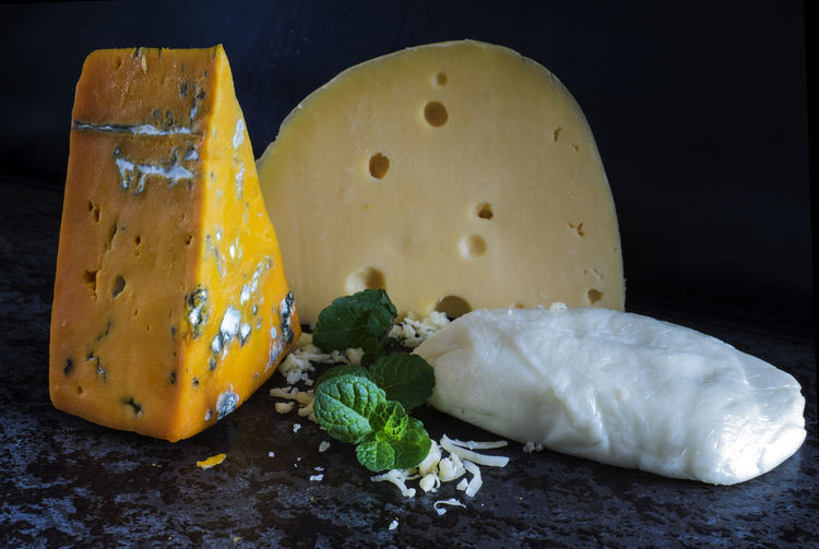 Fresh pieces of cheese (Mozzarella, roquefort, Maasdam) on the stone table Background Black Cheese Food France Fresh Freshness Italy Maasdam Mint Mozzarella Netherlands No People Pieces Roquefort Slate Space Switzerland Table