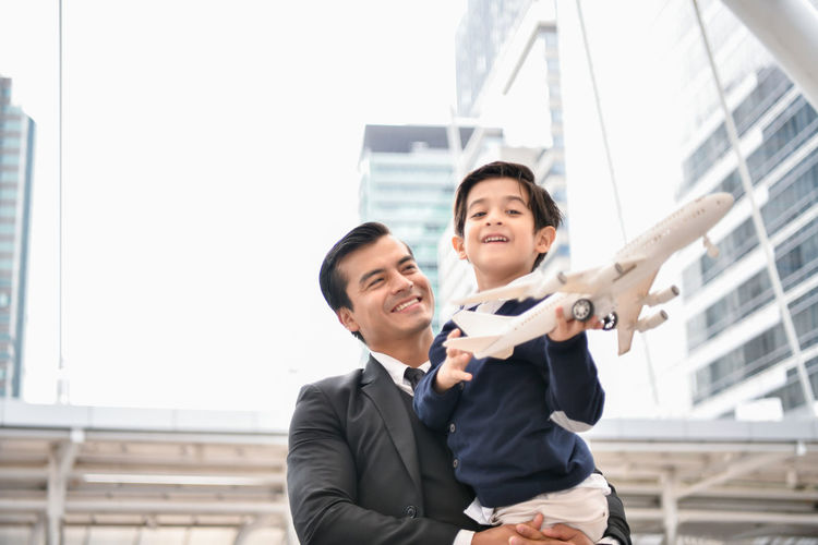 Father carrying son with model airplane in city