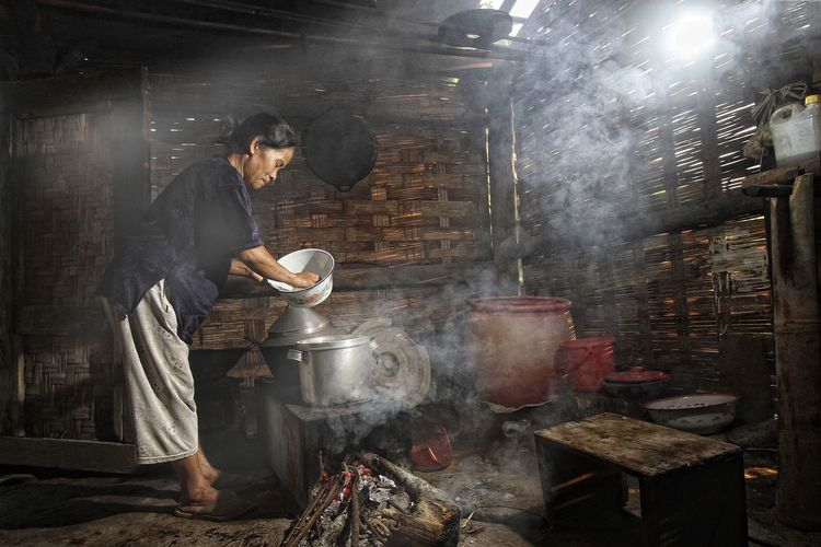 Side view of woman cooking in hut
