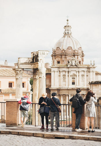 Rear view of tourist standing by railing against roman forum church