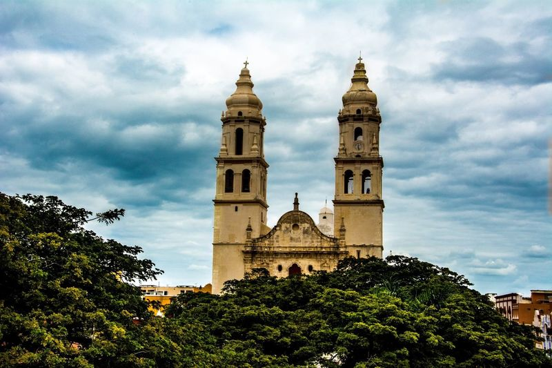 Low angle view of campeche cathedral against cloudy sky
