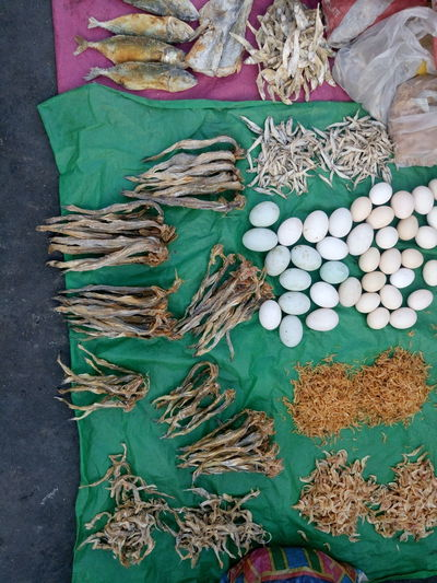 High angle view of dried fish and eggs on plastic at market for sale