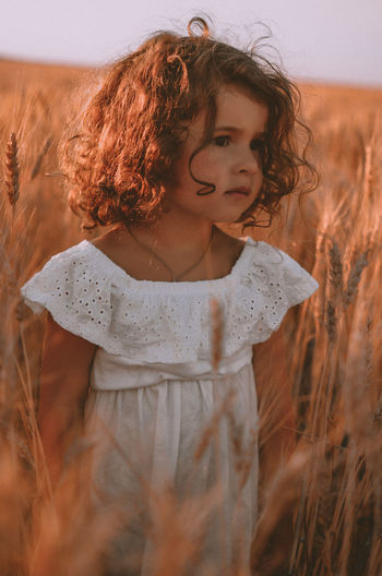 Portrait of cute girl standing on field