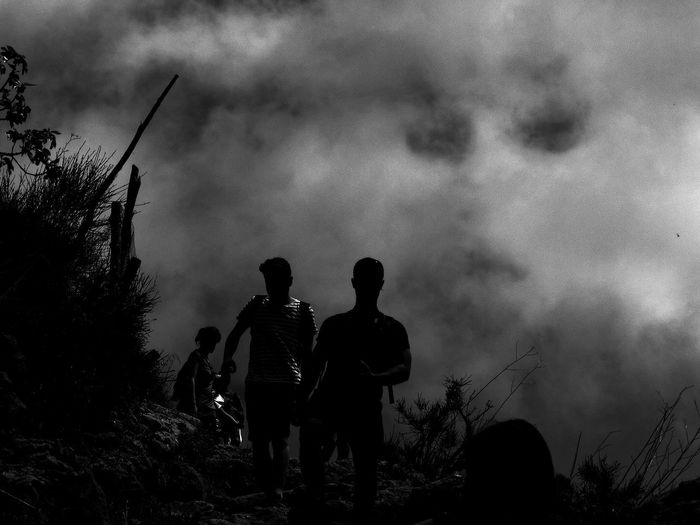 Rear view of silhouette people standing against cloudy sky
