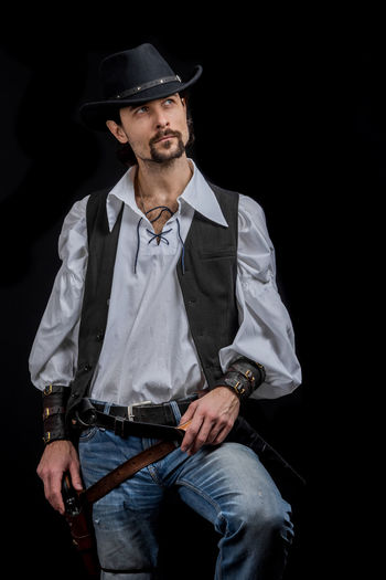 Handsome young man. This is an American cowboy. A vow to a white shirt, brown waistcoat and blue jeans. Black shoes on the feet. Carries a shtyapa, on a belt two pistols. The hair is of medium length; on the face is a beard and mustache. Authentic photo. Culture of America. Cowboy Wild West America American Gun National Authentic Moments Lifestyles Lifestyle One Person Candid Authentic Three Quarter Length Front View Clothing Black Background Hat Adult Men Males  Mid Adult Mid Adult Men Beard Real People Standing