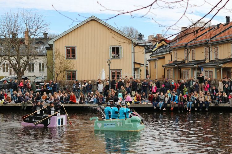 People on boats in canal by buildings in city