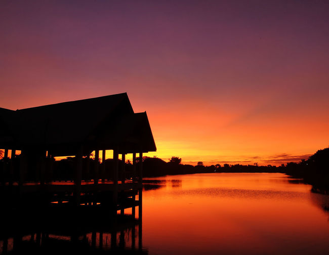 Silhouette houses by lake against romantic sky at sunset