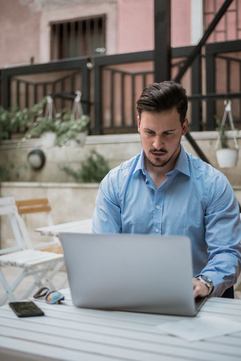 Businessman using laptop while sitting on table outdoors