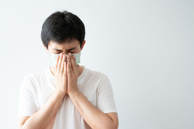 Portrait of young man covering face against white background
