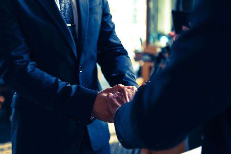 Cropped Image Of Business People Holding Hands