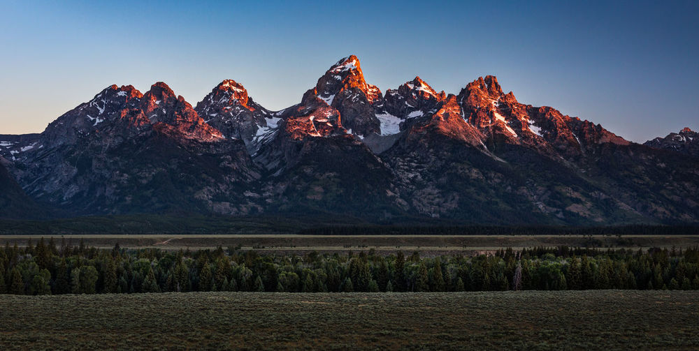 Beginning of the end | Another morning came. Since it was my last day in the Tetons, I didn't mind the cold to catch the sunrise. I arrived at Teton Point Turnout and patiently waited for the sun to come up. When it did, the sun soon cast a gorgeous orange glow on Grand Teton and its adjacent peaks, like it did the previous morning. What a beautiful morning to get excited about the beginning of the end of my road trip, I thought. I snapped a few shots. Then, it was gone. And it meant that it was time to head home. Grand Teton National Park, WY Adventure Beauty In Nature Disappointment Face EyeEm Grand Teton Grand Teton National Park  Landscape Morning Mountain Mountain Peak Mountain Range Mt. Owen Mt. St. Helens  Nature Nez Perce Outdoors Peaks Sky South Teton Sunrise Sunrise Glow Teewinot Mountain Trees Wilderness Wyoming