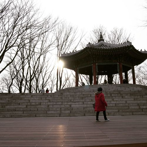 Full length rear view of woman walking at temple against sky
