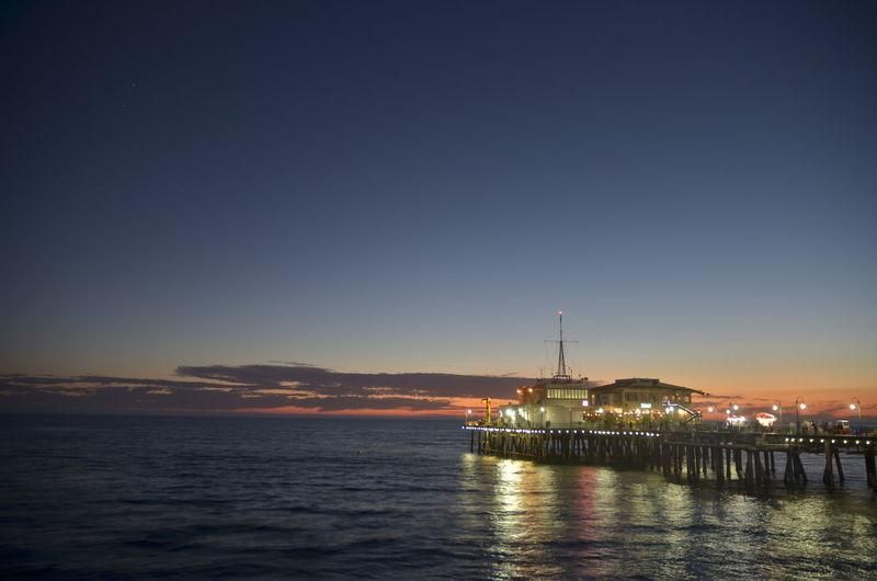 Illuminated Santa Monica Pier Over Sea Against Sky During Sunset