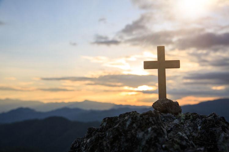 Cross on rock against sky during sunset