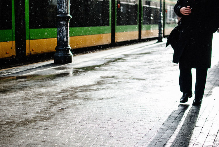 Low Section Of Man Walking On Street During Winter
