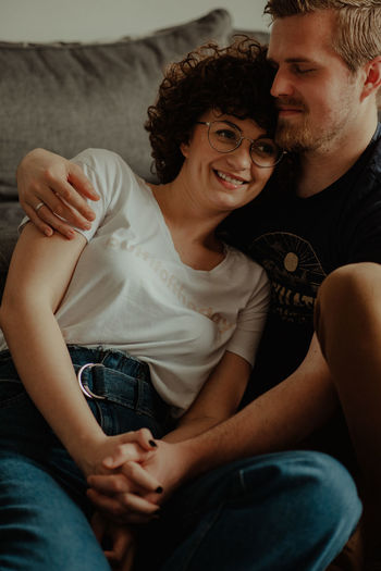 Midsection of couple sitting on sofa